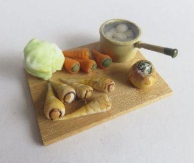 Board with potatoes in enamel pan